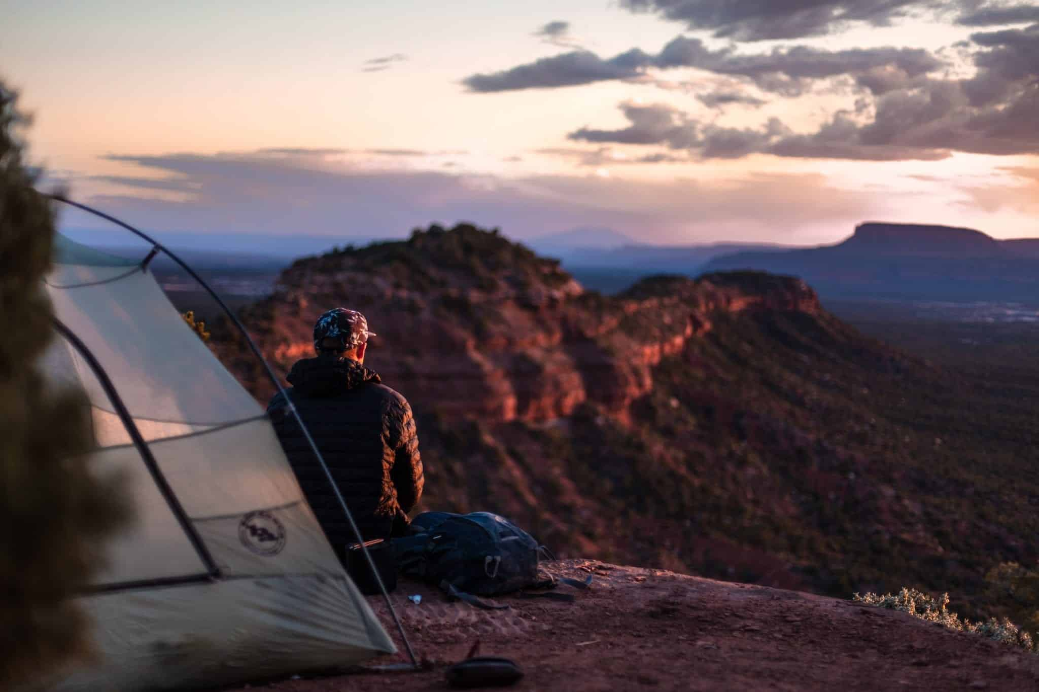 A man sitting in front of a tent looking at canyons in the distance.